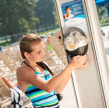 girl at pool getting sunscreen from dispenser