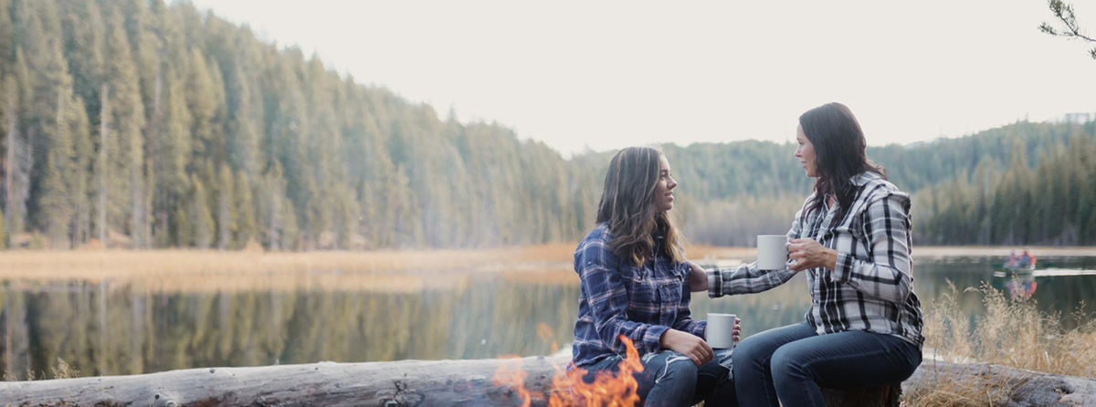 mother and daughter sipping coffee by a fire at the lake