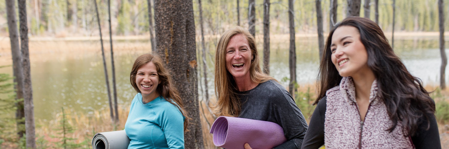 three healthy women walking in the woods with yoga mats