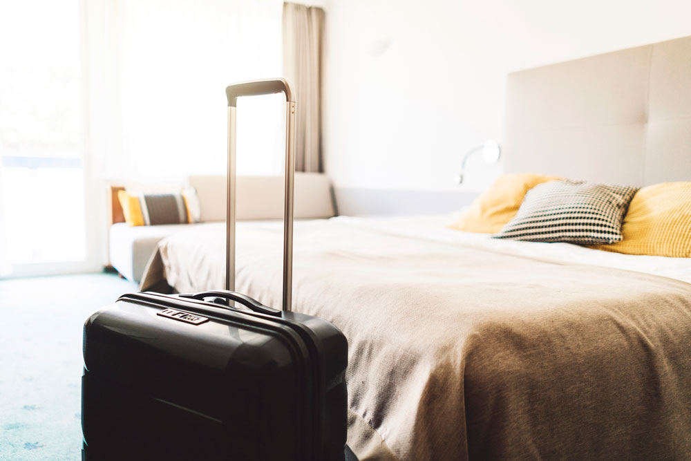 suitcase sitting at the end of bed in hotel room